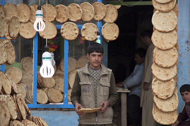 """""""Afghan Bread"""". This image of a bread seller was captured on a morning, in Herat's neighborhood, March 2013. Location: Herat, Afghanistan. (Photo and caption by Ricardo Thome/National Geographic Traveler Photo Contest)"""