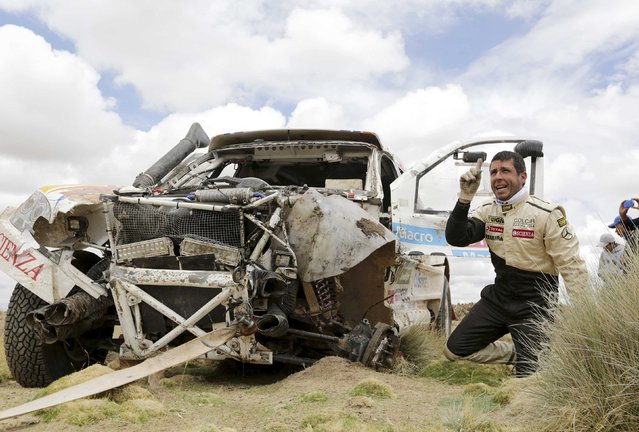 Mercedes driver Juan Manuel Silva of Argentina is seen next to their wrecked car during the 7th stage of the Dakar Rally from Iquique to Uyuni January 10, 2015. (Photo by Daniel Rodrigo/Reuters)