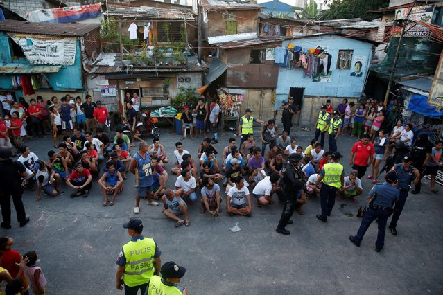 Male residents sit on the ground after they are rounded up by the the police during an anti-drugs operation, in Pasig, Metro Manila in the Philippines, November 9, 2016. (Photo by Erik De Castro/Reuters)