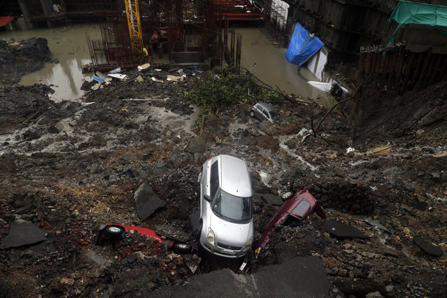 Cars lie buried in debris after the wall of an under construction building collapsed during heavy rains in Mumbai, India, Monday, June 25, 2018. India is currently having its monsoon season. (Photo by Rajanish Kakade/AP Photo)