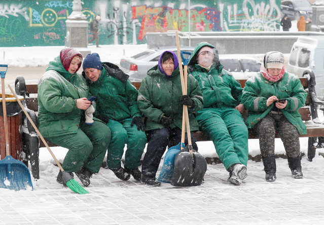 Municipal workers rest as they remove snow during  snowfall in central Kyiv, Ukraine on February 8, 2021. (Photo by Gleb Garanich/Reuters)