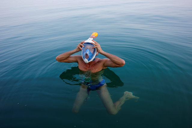 "An environmental activist adjusts his mask while taking part in ""The Dead Sea Swim Challenge"", swimming from the Jordanian to Israeli shore, to draw attention to the ecological threats facing the Dead Sea, in Kibbutz Ein Gedi, Israel November 15, 2016. (Photo by Nir Elias/Reuters)"