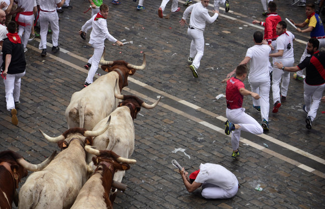 Runners sprint in front of wild cows during the first running of the bulls of the San Fermin festival in Pamplona, Spain, July 7, 2018. (Photo by Vincent West/Reuters)