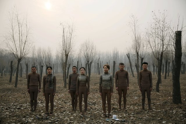 """Models pose before they are painted in camouflage colours to blend in with the background for Chinese artist Liu Bolin's artwork """"Dongji"""", or Winter Solstice, on the second day after China's capital Beijing issued its second ever """"red alert"""" for air pollution, in Beijing, China, December 20, 2015. (Photo by Kim Kyung-Hoon/Reuters)"""