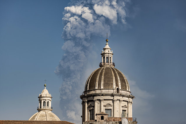Smoke billows from a crater of Mount Etna volcano, background, as the dome of the Catania Saint Agatha cathedral stands out, in Catania, southern Italy, Thursday, March 4, 2021. Mount Etna, the volcano that towers over eastern Sicily, evokes superlatives. It is Europe's most active volcano and also the continent's largest. And the fiery, noisy show of power it puts on for days or weeks, even years every so often, is always super spectacular. (Photo by Salvatore Allegra/AP Photo)