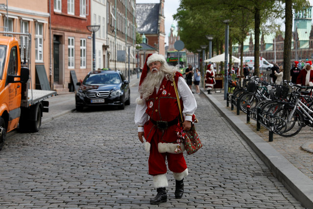 A man dressed as Santa Claus walks through the streets between events for the World Santa Claus Congress, an annual event held every summer in Copenhagen, Denmark, July 23, 2018. (Photo by Andrew Kelly/Reuters)