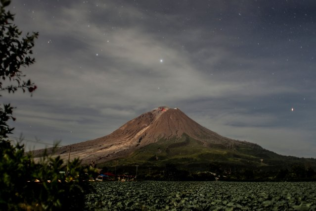 A long exposure picture shows molten lava spilling out from the crater of Mount Sinabung as seen from Naman Teran village in Karo, North Sumatra, Indonesia, 04 March 2021. Mount Sinabung, one of the most active volcanoes in Indonesia, erupted on 02 March, spewing volcanic materials 5,000 meters up in the air. Indonesia sits on the Pacific Ring of Fire, which accounts for 80 percent of the world's seismic activity. (Photo by Dedi Sinuhaji/EPA/EFE)