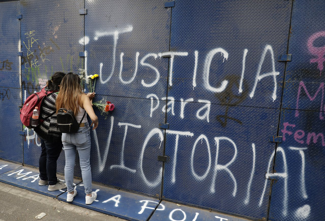 """Young women place flowers on the perimeter wall of the Quintana Roo state offices sprayed with graffiti that reads in Spanish """"Justice for Victoria"""", during a protest in Mexico City, Monday, March. 29, 2021. The demonstrators were protesting the police killing in Tulum, Quintana Roo state, of Salvadoran national Victoria Esperanza Salazar when a female police officer knelt on her back to cuff her. Mexican authorities say an autopsy confirmed that police broke her neck. (Photo by Eduardo Verdugo/AP Photo)"""