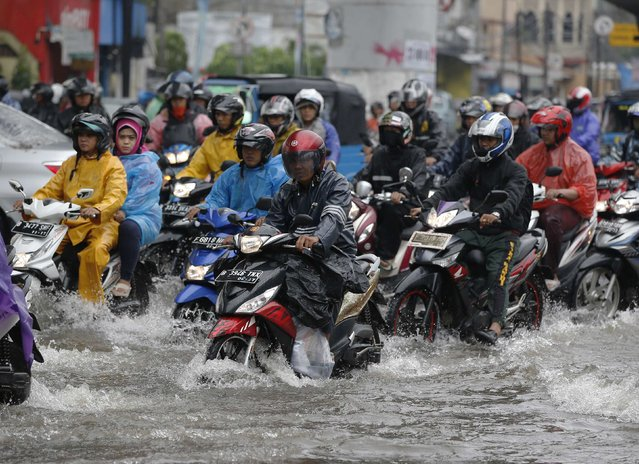 Motorists ride their motorcycles through a flooded intersection after continues heavy seasonal rains have flooded parts of Jakarta February 10, 2015. (Photo by Darren Whiteside/Reuters)