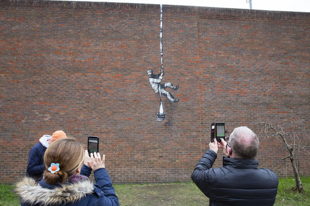 People take pictures of the recent Banksy artwork that has been placed on the side of a redundant prison in Reading, Britain, 05 March 2021. Banksy has taken credit of the artwork of an inmate escaping from a former jail that once housed British playwright Oscar Wilde. (Photo by Joshua Bratt/EPA/EFE)
