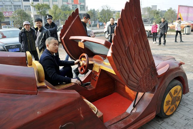 Yu Jietao, 26-year-old wood carver, sits in his homemade wooden car along a street in Guangfeng county of Shangrao, Jiangxi province February 9, 2015. (Photo by Reuters/Stringer)
