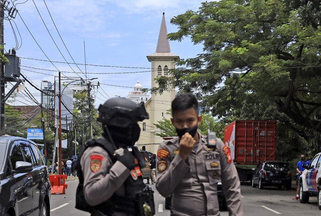 Police officers guard near a church where an explosion went off in Makassar, South Sulawesi, Indonesia, Sunday, March 28, 2021. Police said at least one suicide bomber detonated outside the church on Indonesia's Sulawesi island, wounding several people. (Photo by Yusuf Wahil/AP Photo)