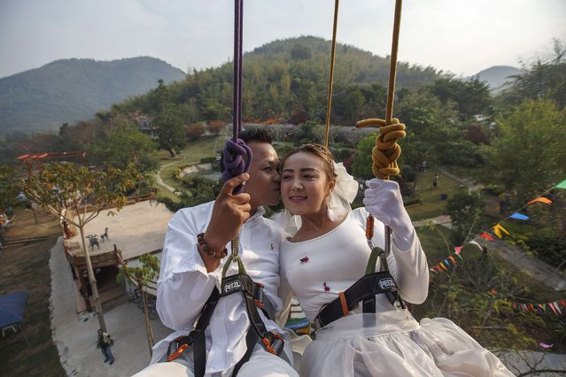 Groom Chaiyut Phuangphoeksuk kisses his bride Prontathourn Pronnapatthun as they are lowered from the top of a climbing wall during their wedding ceremony at a resort in Ratchaburi province February 13, 2015. (Photo by Athit Perawongmetha/Reuters)