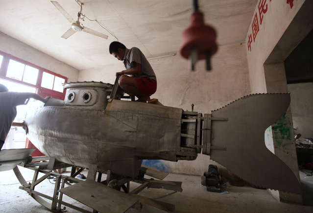 """A worker polishes the surface of an unfinished miniature submarine at a workshop of Zhang Wuyi, a local farmer who is interested in scientific inventions, in Qingling village, on the outskirts of Wuhan, capital of central China's Hubei province August 29, 2011. Zhang has successfully tested his self-made miniature submarine """"Shuguang Hao"""", which is 3.6 m (12 feet) long, 1.8 m (6 feet) high, has a maximum diving depth of 20 m (65 feet), can travel at a speed of 20 km per hour for 10 hours underwater and is shaped as a dolphin. """"I hope to sell my submarine as a civil product with the price of about 100,000 yuan ($15,670) after safety tests, and a merchant has decided to order one in this month"""", Zhang said. (Photo by Jason Lee/Reuters)"""