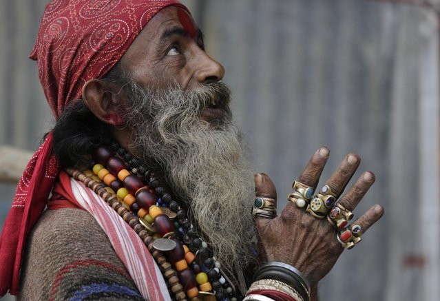 A Hindu holy man on his way to the annual holy dip at Gangasagar, gestures towards a visitor as he rests at a transit camp in Kolkata, India, Wednesday, January 6, 2016. (Photo by Bikas Das/AP Photo)