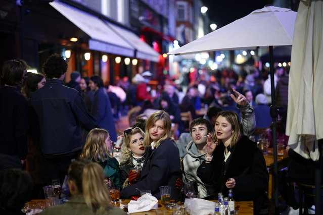 People enjoy the evening at an outside restaurant area in Soho, as the coronavirus disease (COVID-19) restrictions ease, in London, Britain on April 12, 2021. (Photo by Henry Nicholls/Reuters)
