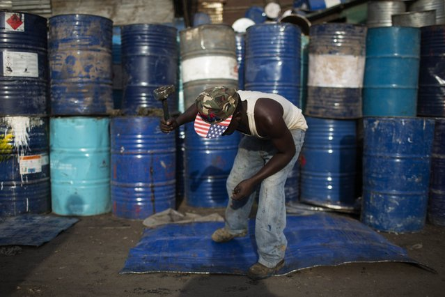A man beats a sheet of metal cut from an oil barrel to use as recycling material in Kamukunji, Nairobi on February 16, 2015. (Photo by Siegfried Modola/Reuters)