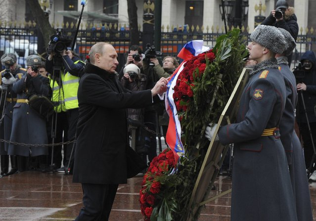 Russian President Vladimir Putin (L) attends a wreath laying ceremony to mark the Defender of the Fatherland Day at the Tomb of the Unknown Soldier by the Kremlin walls in central Moscow February 23, 2015. (Photo by Mikhail Klimentyev/Reuters/RIA Novosti/Kremlin)