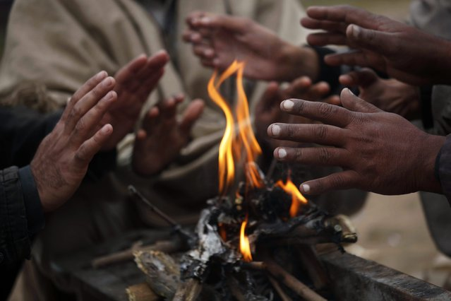 People warm themselves around a fire during a cold, foggy evening in Peshawar, the provincial capital of Khyber Pakhtunkhwa province, Pakistan, 09 December 2015. At least eight persons were reported killed while dozens other sustained injuries due to road accident related to fog across the country. (Photo by Bilawal Arbab/EPA)