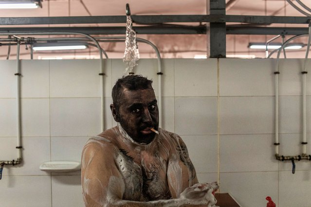 A miner smokes a cigar while showering at the end of his workday on May 10, 2021 in Mieres, Spain. The San Nicolas mine in Spain's northern region of Asturias is the last working coal mine in Spain. At its peak around 2000 people were employed – today, some 200 people work there. (Photo by Manu Brabo/Getty Images)