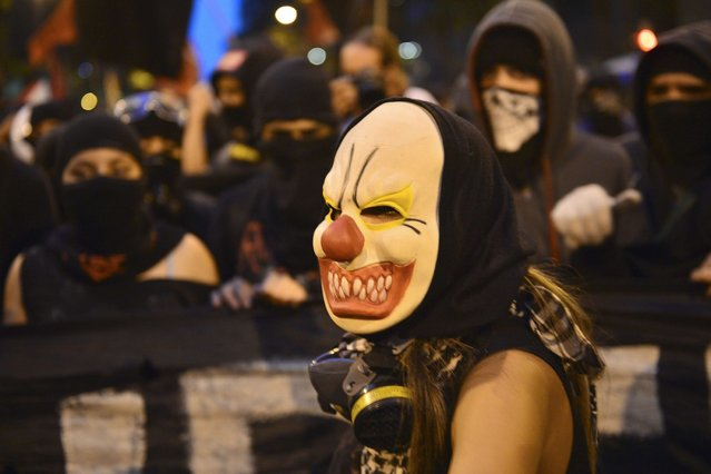 """Activists take part in a """"Teachers' Day"""" protest demanding better working conditions and against police violence, on October 15, 2013 in Rio de Janeiro, Brazil. (Photo by Reuters)"""