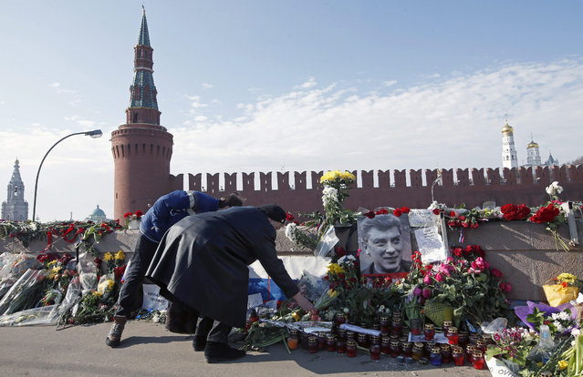 Russian people continue to lay flowers to the place of murder of Russian opposition politician Boris Nemtsov near the Kremlin on Grand Moskvorestsky bridge in Moscow, 09 March 2015. Five suspected in the murder have  been earlier arrested, one died during detention and two more arrested yesterday. All of them are Chechens.  EPA/SERGEI CHIRIKOV