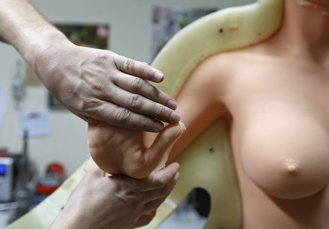 Eric, an employee at the Dreamdoll company, checks a silicone dream doll as he removes it from a mold at their workshop in Duppigheim near Strasbourg, December 2, 2014. (Photo by Vincent Kessler/Reuters)