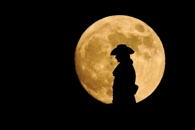 The moon rises in view of a statue of William Penn atop City Hall in Philadelphia, late Wednesday, June 23, 2021. (Photo by Matt Rourke/AP Photo)