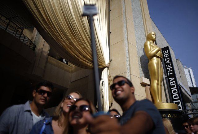 Tourists pose with a selfie stick in front of an Oscar statue before the 87th Academy Awards in Hollywood, California February 18, 2015. (Photo by Lucy Nicholson/Reuters)