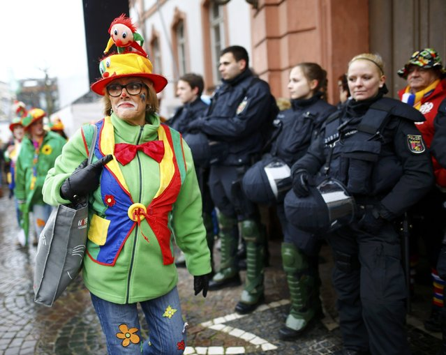 """A reveller walks past police during the traditional """"Weiberfastnacht"""" (Women's Carnival) celebration in Mainz, Germany, February 4, 2016. (Photo by Kai Pfaffenbach/Reuters)"""