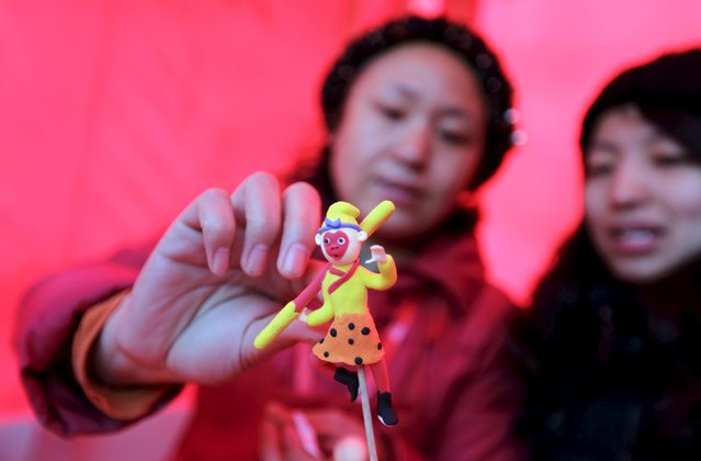 """Folk artist Ma Yueru (L) makes a clay figurine of the """"Monkey King"""" also known as """"Sun Wukong"""" for visitors at a Spring Festival temple fair on the second day of the Chinese Lunar New Year of the Monkey in Beijing, China, February 9, 2016. (Photo by Jason Lee/Reuters)"""