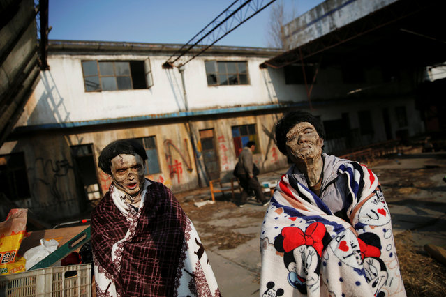 Actors wrapped in blankets look on at the set of the post-apocalyptic movie Zombie Era at an abandoned factory complex in Langfang, Hebei province, China December 16, 2016. (Photo by Damir Sagolj/Reuters)
