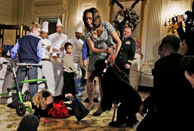 First lady Michelle Obama reacts as Ashtyn Gardner, 2, from Mobile, Alabama, loses her balance while greeting Sunny, one of the presidential dogs, as children of military families participate in a holiday arts and crafts event in the State Dining Room at the White House, on December 4, 2013. (Photo by Charles Dharapak/Associated Press)