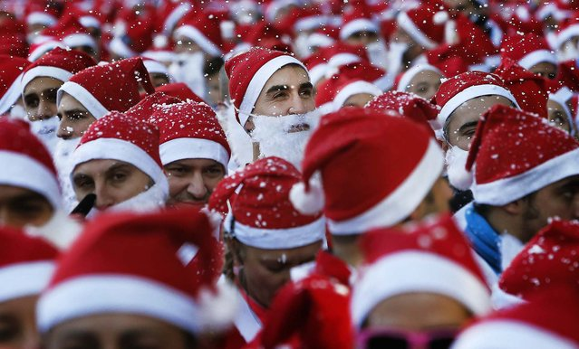 "Revelers dressed as Santa Claus run during the ""mini-marathon"" in Madrid. (Photo by Andres Kudacki/Reuters)"
