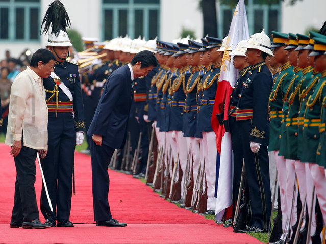 Japanese Prime Minister Shinzo Abe bows his head before the Philippine flag during a welcome ceremony at the presidential palace in Manila, Philippines January 12, 2017. (Photo by Erik De Castro/Reuters)