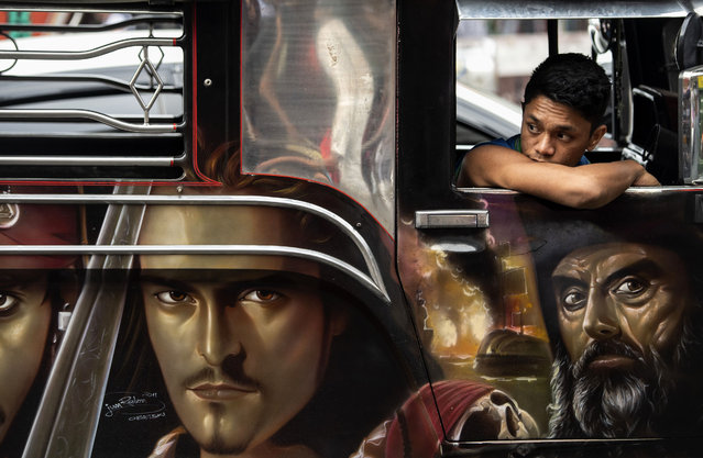 This picture taken on January 13, 2019 shows custom artwork on the side of a jeepney as a driver's assistant waits for passengers during rush hour in Manila, Philippines. Hand-painting custom decor on jeepneys adorned with images of everything from Batman to babies, as well as disco lights and chrome wheels, have for decades provided cheap transport for millions. But pollution and safety concerns have led to a modernisation programme, with jeepneys 15 years or older to be taken off the streets by 2020. (Photo by Noel Celis/AFP Photo)