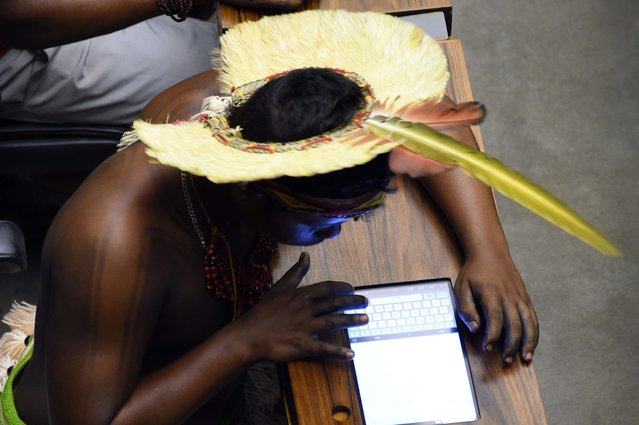 A Brazilian native checks his tablet computer during a session to honor native people at the National Congress in Brasilia, during the National Mobilization Week on April 16, 2015. Several Brazilian tribes are taking part in the so-called Free Land camp. (Photo by Evaristo Sa/AFP Photo)