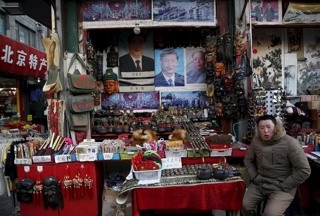 A vendor selling posters bearing the images of China's President Xi Jinping (C) and Chinese late chairman Mao Zedong (R) and other goods wait for customers at a shopping district near the Great Hall of the People, where the National People's Congress will be held, in Beijing, China, February 26, 2016. (Photo by Kim Kyung-Hoon/Reuters)