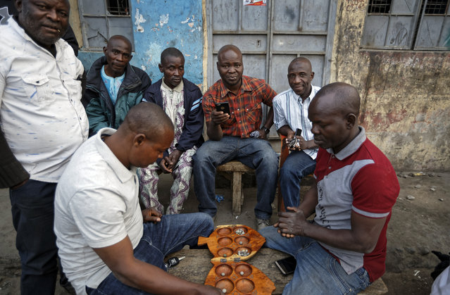 Nigerians play the board-game Ayoayo over beers at a street-side bar in the predominantly-Christian neighborhood of Sabon Gari in Kano, northern Nigeria Saturday, February 16, 2019. (Photo by Ben Curtis/AP Photo)