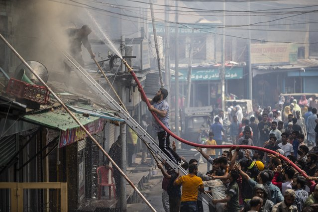 Indian firefighters and civilians work to extinguish a fire in Srinagar, Indian controlled Kashmir, Tuesday, September 7, 2021. A mosque and some buildings where damaged in the fire. No casualties were reported. (Photo by Mukhtar Khan/AP Photo)