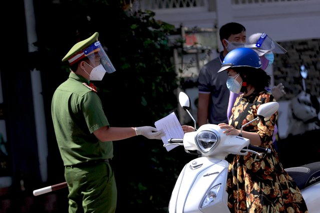 A policeman hands back the travel permit to a commuter after checking at a street checkpoint in Vung Tau, Vietnam on Monday, September 6, 2021. (Photo by Hau Dinh/AP Photo)