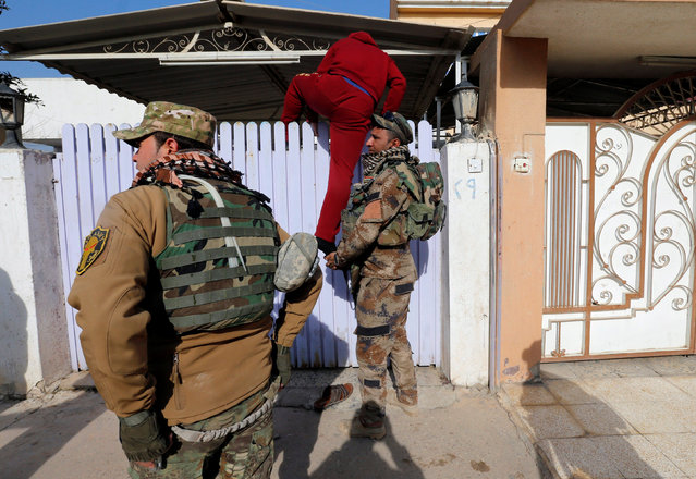 A man climbs over a fence to open it for the Iraqi army members during an operation to search for weapons in the Arabi neighborhood in Mosul, Iraq January 26, 2017. (Photo by Muhammad Hamed/Reuters)
