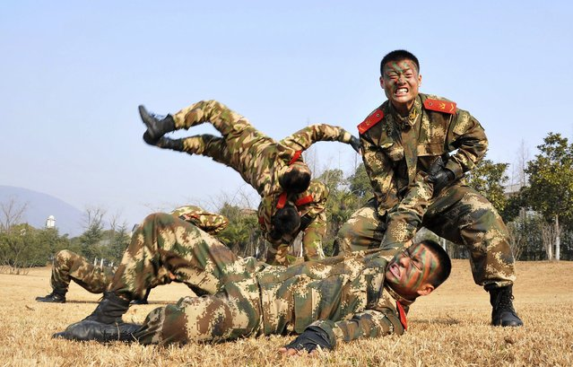 Paramilitary policemen wrestle as they take part in a winter training session at a military base in Chaohu, Anhui province, January 20, 2014. (Photo by Reuters/China Daily)