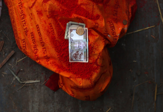 Nepalese currency is placed on the body of an earthquake victim who died in the recent earthquake during the cremation ceremony at the Pashupatinath temple, on the banks of Bagmati river, in Kathmandu, Nepal, Monday, April 27, 2015. (Photo by Manish Swarup/AP Photo)