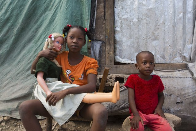 In this December 3, 2016 photo, 11-year-old Neissa Bonissant cradles her doll Vanessa while sitting next to her 4-year-old brother Olivier, in front of their shelter in the Delmas tent camp set up nearly seven years ago for people displaced by the 2010 earthquake, in Port-au-Prince, Haiti. The number of people in these makeshift communities has declined since the aftermath, but those who remain are a stubborn reminder that this impoverished country has yet to fully recover. (Photo by Dieu Nalio Chery/AP Photo)
