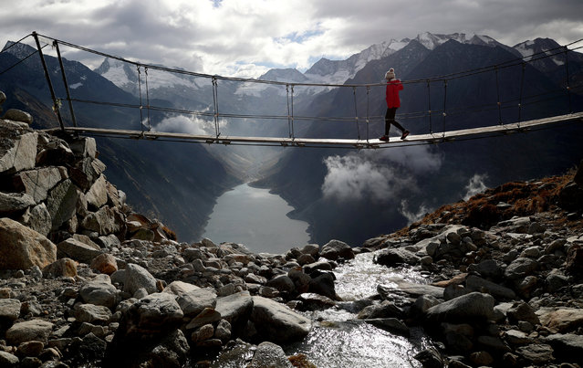 A woman walks on a swing bridge beyond Schlegeis reservoir on a sunny autumn day near the alpine village of Ginzling, Austria October 21, 2018. (Photo by Lisi Niesner/Reuters)