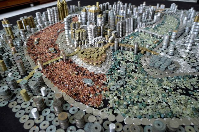 This photo taken on April 29, 2015 shows a replica of Chongqing built with coins and agate stones by Chongqing local resident He Peiqi at his home in China's southwest Chongqing municipality. (Photo by AFP Photo/Stringer)