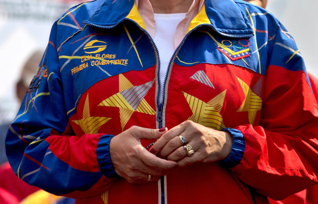 "Venezuela's first lady Cilia Flores wears a jacket made in the colors of Venezuela's flag during a May Day rally in Caracas, Venezuela, Friday, May 1, 2015. Flores' jacket reads her name, along with her official title ""Primera Combatiente"". Instead of first lady, Flores' goes by the title ""First Fighter"". (Photo by Fernando Llano/AP Photo)"