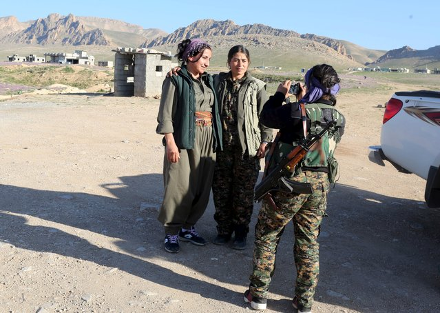 A female Kurdistan Workers Party (PKK) fighter takes a photo with her mobile phone as others visit from another base, in Sinjar, March 10, 2015. (Photo by Asmaa Waguih/Reuters)