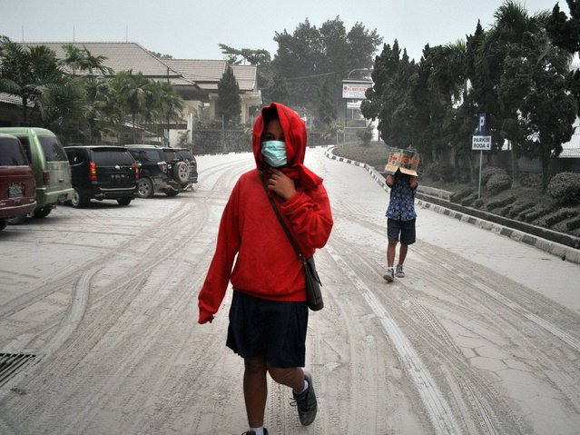 Indonesian students walk on a street covered with volcanic ash following an eruption of Mount Kelud, in Yogyakarta. (Photo by Slamet Riyadi/AP Photo)